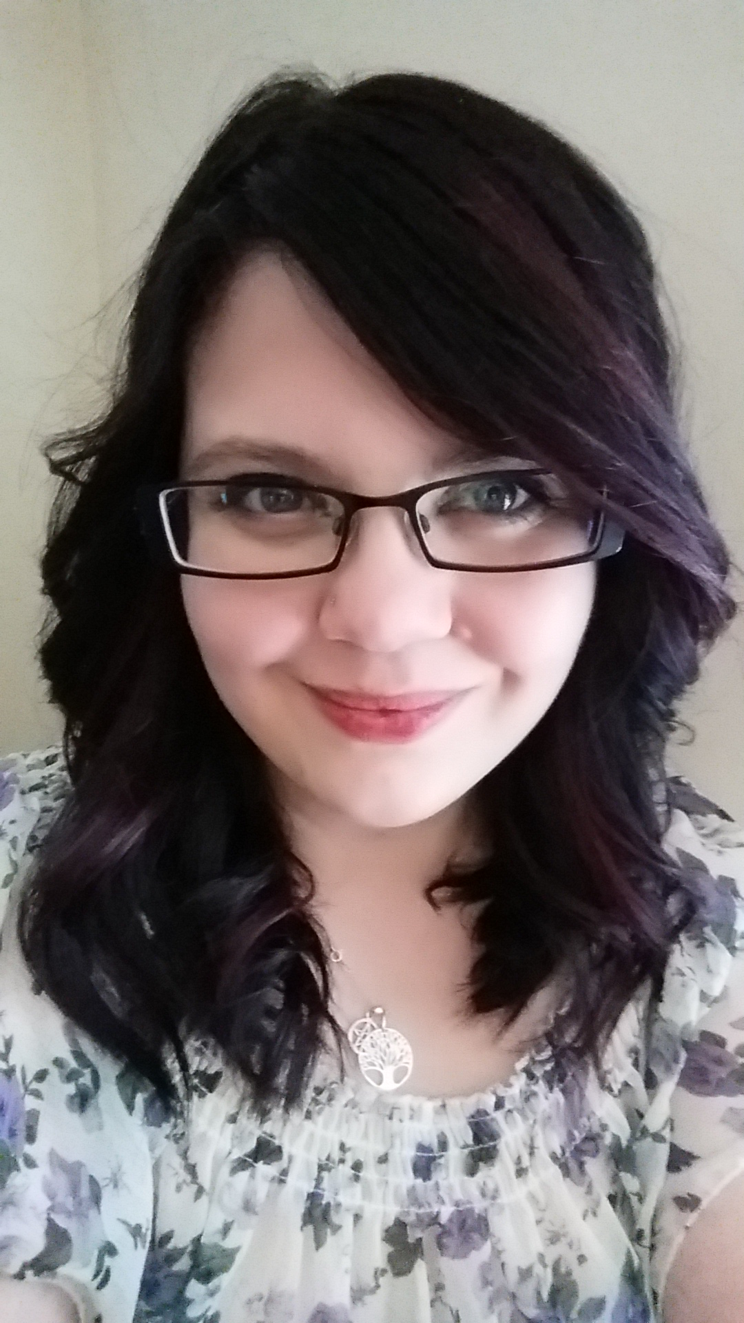 Image Description: A picture of Aerilyn who has white pale skin and blue eyes and is slightly smiling. She is wearing black squareish framed glasses. Her hair is purple with lighter purple highlights and is wearing a necklace with a pentagram and the tree of life. She is wearing a white shirt with purple flowers and green leaves. The background is beige.