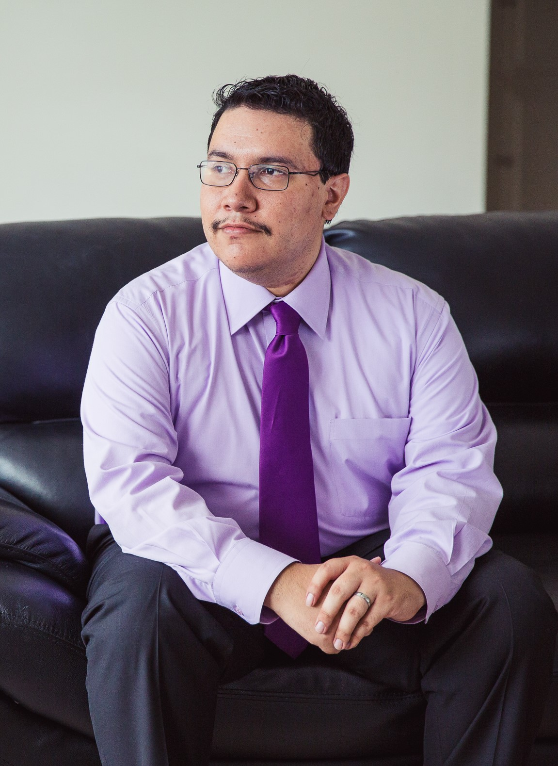 Image Description: A picture of Juan who has tanned skin with a mustache and dark short hair. He is sitting on a black leather couch facing away from the camera with his hands clasping each other, and the wall behind him is beige. He is wearing black and silver glasses, a light purple dress shirt with a darker purple tie, on his left hand ring finger he is wearing a silver wedding band.